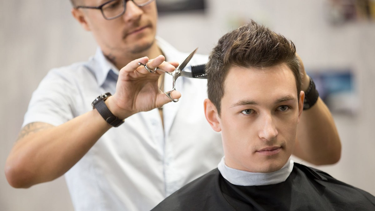 A young man getting a traditional haircut at the barber.